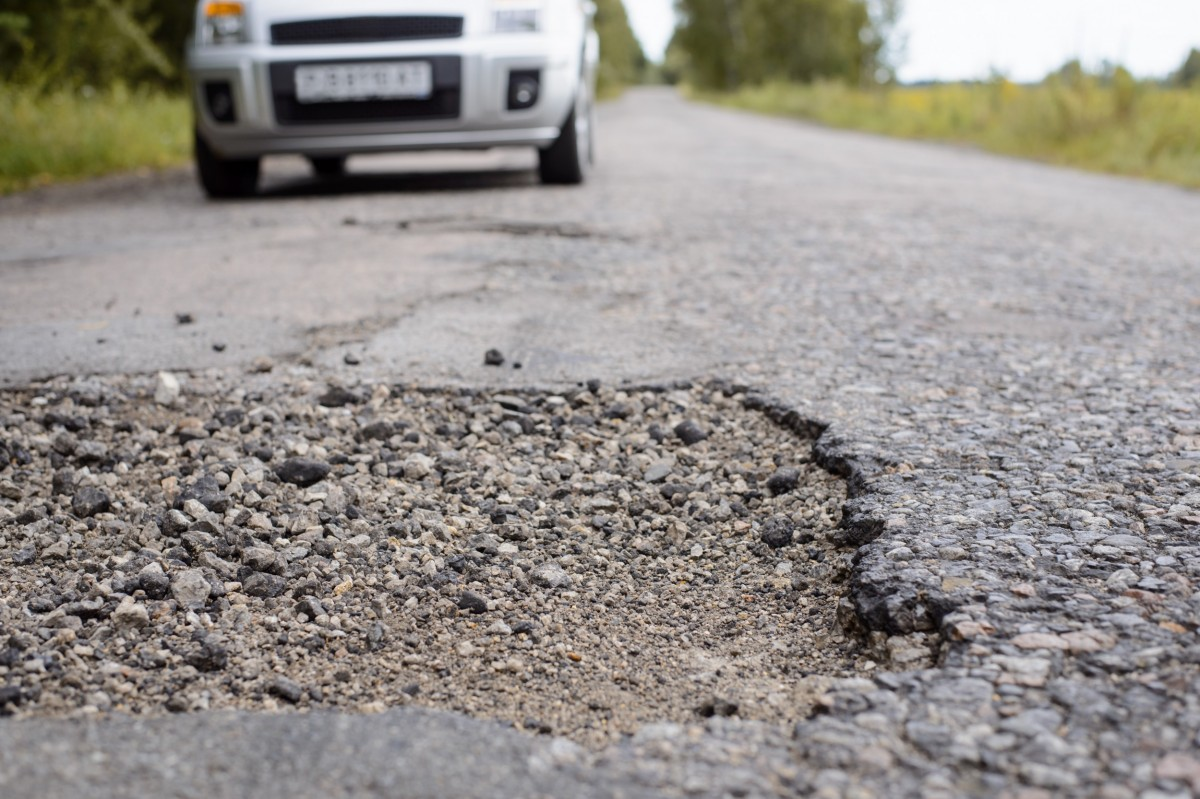 pothole in road with car in the background
